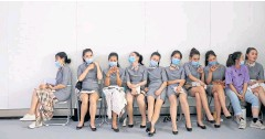 ??  ?? A MO­MENT TO BREATHE: Ush­ers wear­ing face masks take a rest on the side­lines of the Auto China show, in Bei­jing, China, yes­ter­day.