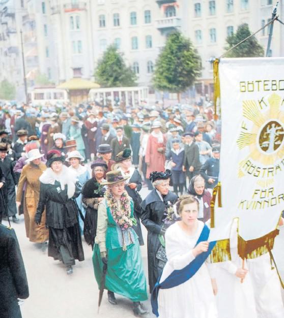 ?? Bild: Hjörnearkivet ?? Rösträttsdemonstration i Göteborg den 2 juni 1918. Frigga Carlberg, klädd i svart, är synlig i första ledet efter standarbärarna. (Bilden är tagen med svartvit film och är färglagd i efterhand av Marina Amaral)