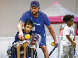 ??  ?? Bourns helps Evan Cruz, 13, with his swing technique as he demonstrates wheelchair tennis at Abilities Expo, held in August at NRG Center.
