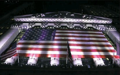 ?? Peter Morgan/Associated Press ?? An American flag hangs on the front of the New York Stock Exchange in February. European stocks declined while most Asian markets rose Friday, ahead of the first round of voting in France's presidential election.