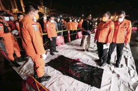 ?? DITA ALANGKARA AP ?? The Chief of National Search and Rescue Agency Bagus Puruhito, second right, stands with his staff near a body bag containing debris found in the water off Java Island where a Sriwijaya Air passenger jet has lost contact with air traffic controllers shortly after take off, at Tanjung Priok Port in Jakarta, Indonesia, early Sunday.