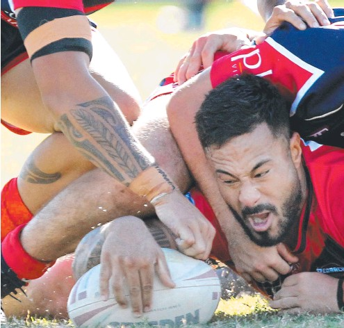 ??  ?? Mudgeeraba Redbacks reserve grade player Thomas Tapu overpowers multiple defenders to score a try against Runaway Bay.