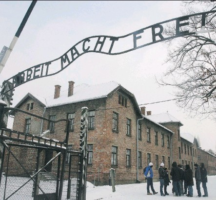 ?? THE ASSOCIATED PRESS ?? Tourists pause near the main entrance and a replica of the inscription 'Arbeit Macht Frei' (Work Sets You Free) at the former Nazi death camp AuschwitzBirkenau, in Oswiecim, southern Poland. Max Eisen lost 60 family members to the camps.