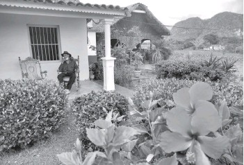 ??  ?? Eduardo Hernandez, owner of a private restaurant and a tobacco cultivator, smokes a cigar outside his house in Vinales, Cuba.