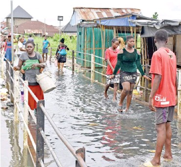 ?? Photo: NAN ?? Residents use a flooded bridge to access their homes at Akienfa community in Bayelsa State yesterday