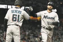 ?? Thearon W. Henderson / Getty Images ?? Miami's Jose Devers congratulates Jon Berti after his solo home run tied the game in the seventh inning.