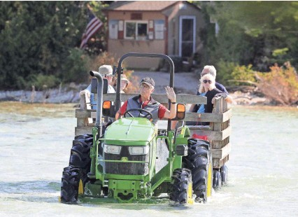?? PHOTOS BY WM. GLASHEEN / USA TODAY NETWORK-WISCONSIN ?? Maritime Museum volunteer Ben Coopman ferries visitors across the Cana Island causeway with a tractor last month in Baileys Harbor. High water levels now routinely flood the causeway.