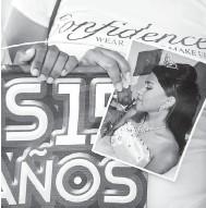 ?? — Gambar AFP ?? MENYAYAT HATI: Gadis membawa poster dan gambar Falcon ketika menghadiri acara keagamaan di La Mision, negeri Portuguesa kelmarin.