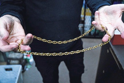 """?? HARRISON HILL/USA TODAY ?? Glenn Sorgenstein holds a gold necklace inside of his store, Wilshire Coin, in Santa Monica, Calif. """"Some people would prefer to wear their wealth,"""" Sorgenstein said."""