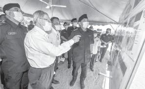 ?? — Gambar Bernama ?? TINJAUAN: Abdul Hamid (tiga kanan) bersama Menteri di Jabatan Perdana Menteri (Ekonomi) Datuk Seri Mustapa Mohamed (dua kiri) melihat pelan pembinaan Ibu Pejabat Polis Daerah (IPD) Jeli yang baharu ketika lawatan kerja di tapak pembinaan IPD Jeli semalam.