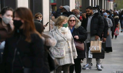 ?? Photograph: Neil Hall/EPA ?? Shoppers queueing on Oxford Street in London as non-essential shops reopened on 12 April 2021.
