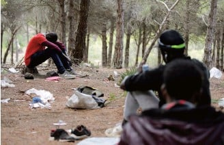 ??  ?? African migrants seated in a hiding place in the Moroccan mountains near the port city of Tangier.