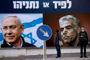 ?? The Associated Press ?? ■ In this March 14 file photo, people stand in front of an election campaign billboard for the Likud party showing a portrait of its leader Prime Minister Benjamin Netanyahu, left, and opposition party leader Yair Lapid, in Ramat Gan, Israel. Israel's President Reuven Rivlin has tapped Lapid to form a new government, a step that could lead to the end of Netanyahu's lengthy rule.