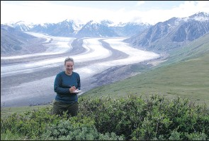 ?? Cath erine Henry, Special to The Journal ?? University of Alberta biologist Isla Myers-smith examines the spread of summer shrub cover above the Kaskawalsh Glacier in the Yukon.