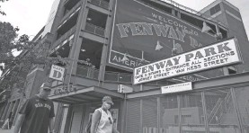 ?? AP ?? Two fans walk past Boston's Fenway Park before a Red Sox game July 24.