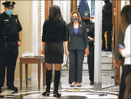 ?? Chip Somodevilla Getty I mages ?? HOUSE SPEAKER Nancy Pelosi and other lawmakers face additional security screening to enter the House chamber on Tuesday. At least a dozen Republicans pushed past or went around detectors. One refused to let the police search her bag after setting off the detector.
