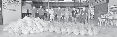??  ?? TERIMALAH: Liu memberikan sumbangan bantuan makanan sambil ditemani AJK Kampung Bumbok.