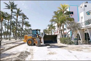 ?? El Nuevo Herald/TNS ?? Miami Beach workers remove sand from Ocean Drive on Sept. 12, right after Hurricane Irma hit. Federal law currently prohibits local governments from importing sand from foreign countries.