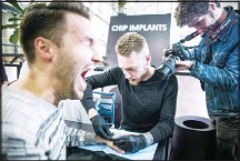 ??  ?? A man reacts as he gets a chip implant in his hand during a chip implant event in Epicenter, a technological hub in Stockholm on Jan 18, 2018. (AFP)