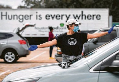 ?? Photos by Marie D. De Jesús / Staff photographer ?? Houston Food Bank volunteer Cecilie Tindlund directs traffic during a meal distribution event at NRG Park on Sunday.
