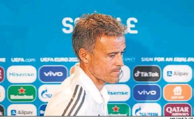 ?? PABLO GARCÍA / EFE ?? Luis Enrique pasa por el cartel de Sevilla en la sala de prensa del Estadio de la Cartuja.