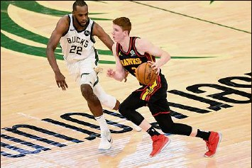 ?? Patrick Mcdermott / Getty Images ?? Shenendehowa graduate Kevin Huerter of the Atlanta Hawks brings the ball up court Friday against Khris Middleton of the Milwaukee Bucks. Huerter had eight points in 30 minutes.