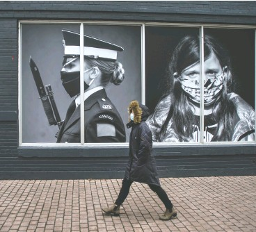 ?? PETER J. THOMPSON / NATIONAL POST ?? A pedestrian wearing a mask walks past photos by photograph­ers Dave Chan, on the left, and Jennifer Long at a Toronto exhibit called Portraits In Covid Times: