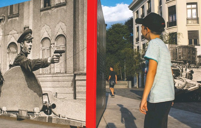 ?? PHOTOS BY MICHAEL ROBINSON CHAVEZ/THE WASHINGTON POST ?? CLOCKWISE FROM TOP: A man with a swastika tattooed on his arm walks down a street in Bucharest, Romania. Protesters in Warsaw object to what they see as the anti-constitutional push of the Polish government. A boy in Bucharest looks at a photography exhibit commemorating the Soviet invasion of Prague in 1968.