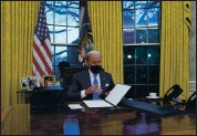 ?? EVAN VUCCI — THE ASSOCIATED PRESS ?? President Joe Biden signs his first executive orders in the Oval Office of the White House on Wednesday.