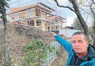 ??  ?? Gemeinderat Anton Mahdalik (FPÖ) zeigt auf das kontroverse Bauprojekt