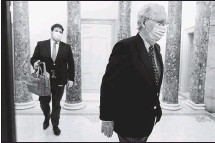 ?? THE ASSOCIATED PRESS ?? Followed by a staffer, Senate Majority LeaderMitch McConnell (right) left the Capitol last week in Washington.