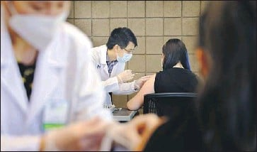 ?? Christina House Los Angeles Times ?? SARITH MEY, center left, administers a COVID-19 vaccine to Cal State Dominguez Hills student Fritzi Bui on campus Thursday. In L.A. County, 75.7% of residents 12 and older have received at least one dose of vaccine.