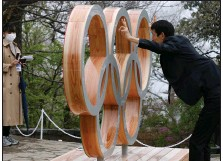 ?? (AP/Kim Kyung-Hoon) ?? A man poses with a display of the Olympic symbol Wednesday on Mount Takao in Hachioji, located west of Tokyo. Wednesday marked 100 days before the scheduled start of the Tokyo Olympics.