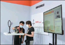 ?? MAO XUQIAN / FOR CHINA DAILY ?? A visitor (right) tries out a livestreamed class broadcast from a studio of online tutoring firm Yuanfudao at the China International Fair for Trade in Services on Sept 6.
