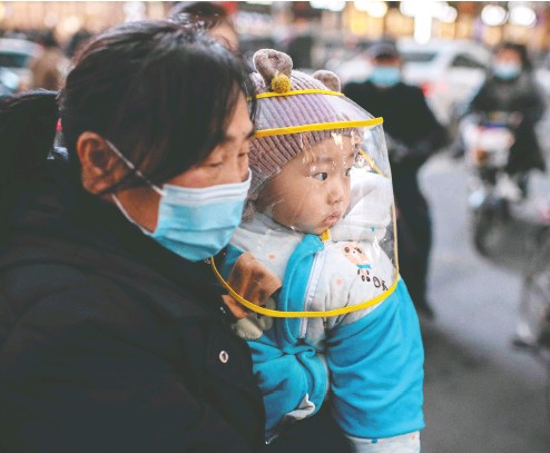 ?? NICOLAS ASFOURI / AFP VIA GETTY IMAGES ?? Mother and baby take a breath in Wuhan on Wednesday, the day before a team of WHO experts is expected to land to