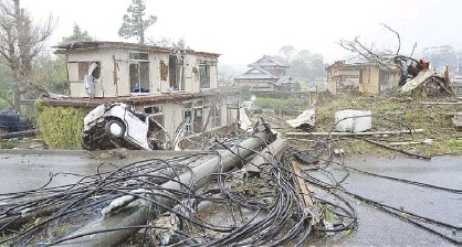 ?? REUTERS ?? De­stroyed houses, cars and power poles, which ac­cord­ing to lo­cal me­dia were be­lieved caused by a tor­nado, are seen in Ichi­hara, east of Tokyo on Sat­ur­day.
