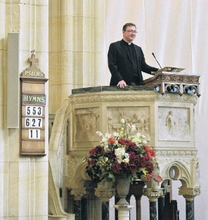 ?? PHOTO: LINDA ROBERTSON ?? Positive future . . . The Very Rev Dr Tony Curtis, dean of St Paul's Cathedral, Dunedin, stands in the pulpit. A streamlined speaker, part of a sound system installed after last year's fire, blends in with the stone column at the left of the hymn board.