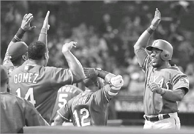 ?? Jae C. Hong/The Associated Press ?? Rangers shortstop Elvis Andrus (right) celebrates his third-inning homer against the Angels with teammates.