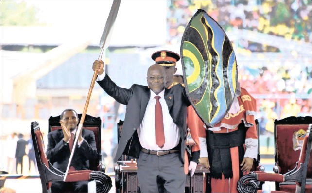 ?? PICTURE: KHALFAN SAID/AP ?? CHANGE, HIS WAY: Tanzanian President John Pombe Magufuli holds up a ceremonial spear and shield to signify the beginning of his presidency, at Uhuru Stadium in Dar es Salaam, Tanzania on November 5, 2015. Intolerance for corruption and thrift has won...