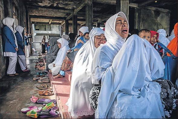 ?? ULET IFANSASTI / GETTY IMAGES ?? Arriba, escenas de dolor ayer en Banda Aceh, una de las zonas más afectadas por el tsunami