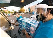 ?? Genaro Molina Los Angeles Times ?? MASKS, hand sanitizer and other supplies to fight the pandemic are distributed in Hollywood in 2020.