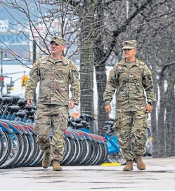 ??  ?? National Guard officers in New York, America's hardest-hit state