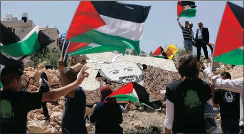 ??  ?? Palestinian activists stand around a mosaic portrait of Marwan Barghouti near an Israeli military installation in the West Bank city of Ramallah. Picture: AP