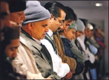 ??  ?? Asif prays with other men in the mosque's lofty main hall, carpeted in grey and green. Women take part in a separate room.