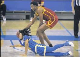 ?? MARK J. TERRILL — THE ASSOCIATED PRESS ?? UCLA's Tyger Campbell dives for a loose ball as USC's Evan Mobley corrals it the second half Saturday at Pauley Pavilion. USC won 64-63 to keep its conference title hopes alive.
