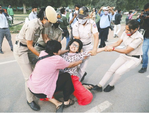 ?? Anushree Fadna vis / Reuters ?? A demonstrator is detained by police Wednesday during a protest in New Delhi after the cremation of a rape victim.