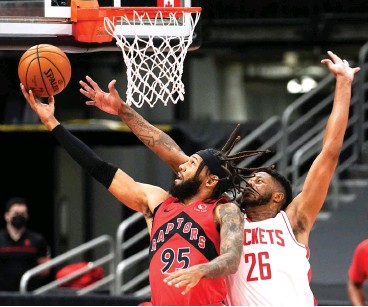 ?? AP Photo/Chris O'Meara ?? Toronto Raptors forward DeAndre' Bembry (95) goes for a layup in front of Houston Rockets center Justin Patton (26) during the first half Friday in Tampa, Fla.