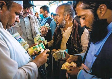 ?? Marcus Yam Los Angeles Times ?? TRADERS ENGAGE in negotiations at the Sarai Shahzadah currency exchange market in Kabul, Afghanistan, which opened Sept. 4 for the first time since the Taliban regained control of the country last month.