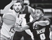 ?? THE ASSOCIATED PRESS ?? VCU's JamirWatkins passes the ball as Penn State's Trent Buttrick defends during the Nittany Lions'home winWednesday night. Watkins scored 5 points.