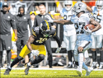 ?? Benjamin Hager Las Vegas Review-journal @benjaminhphoto ?? Raiders cornerback Trayvon Mullen runs back an interception while Steelers wide receiver Diontae Johnson attempts to tackle him during the first half on Sunday.